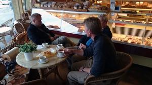 Förmiddagskaffe i Houffalize. Johan försöker kommunicera med omvärlden med Ola kritiskt granskar hans ansträngningar.